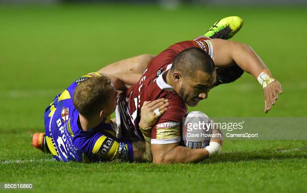 Wigan Warriors' Thomas Leuluai is tackled by Warrington Wolves' Kevin Brown during the Betfred Super League Round 4 match between Warrington Wolves...