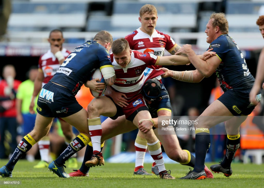 Wigan Warriors' Tom Davies tries to break free of the Warrington line during the Betfred Super League, Magic Weekend match at St James' Park, Newcastle.