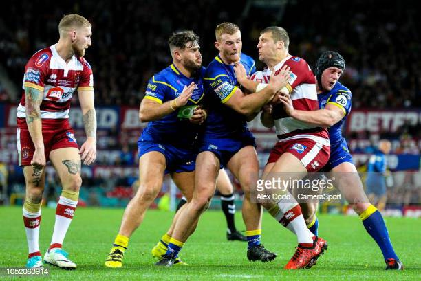 Wigan Warriors' Tony Clubb is tackled by Warrington Wolves' Joe Philbin Jack Hughes and Chris Hill during the Betfred Super League Grand Final match...