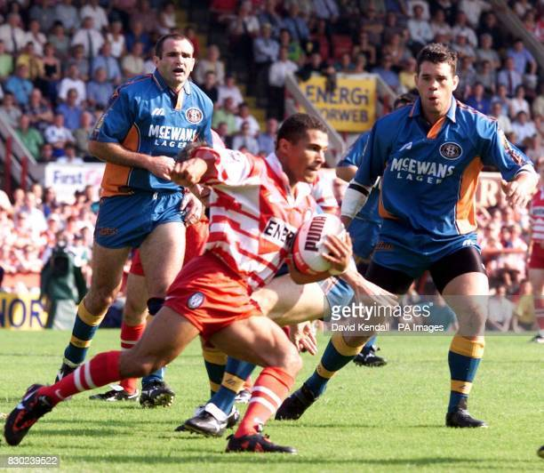 Wigan's Jason Robinson sets up Wigan Warriors first try watched by St Helens Chris Joynt and Des Clark at Wigan's Central Park ground