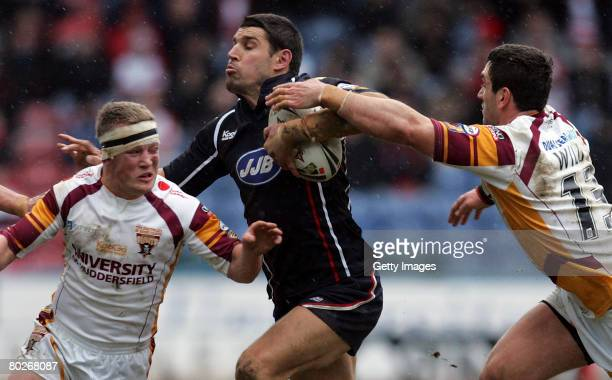 Wigan's Trent Barrett runs between Hudderfields Luke Robinson and Stephen Wild during the Engage Super League match between Huddersfield Giants v...
