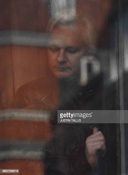 Wikileaks founder Julian Assange appears at the window of the balcony prior to making an address to the media at the Embassy of Ecuador in London on...