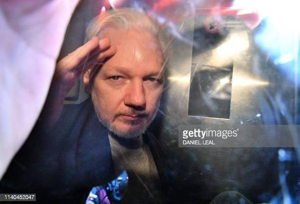 WikiLeaks founder Julian Assange gestures from the window of a prison van as he is driven out of Southwark Crown Court in London on May 1 after...