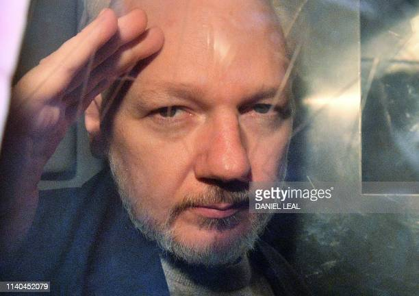 TOPSHOT WikiLeaks founder Julian Assange gestures from the window of a prison van as he is driven out of Southwark Crown Court in London on May 1...