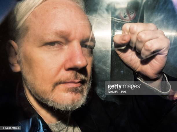 WikiLeaks founder Julian Assange gestures from the window of a prison van as he is driven into Southwark Crown Court in London on May 1 before being...