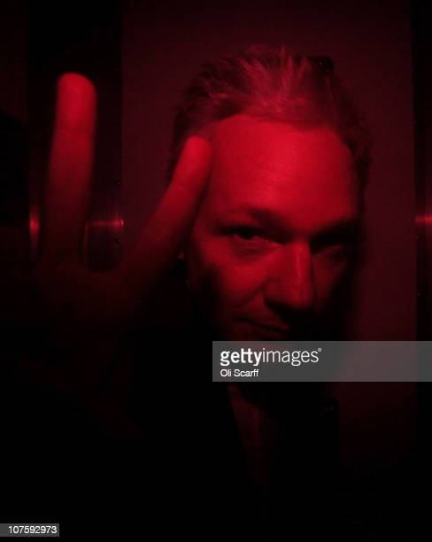 Wikileaks founder Julian Assange gestures inside a prison van with red windows as he leaves Westminster Magistrates Court on December 14, 2010 in...