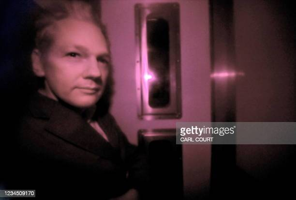 Wikileaks founder Julian Assange is pictured through the heavily tinted windows of a police vehicle as he arrives at Westminster magistrates court in...