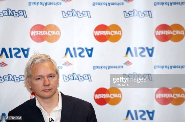 Wikileaks founder Julian Assange looks on as he stands in front of a selection of inverted banking company logos during a press conference at the...