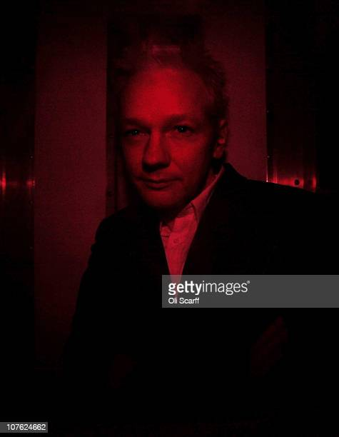 Wikileaks founder Julian Assange looks out from inside a prison van with red windows as he arrives at the Royal Courts of Justice on December 16 2010...