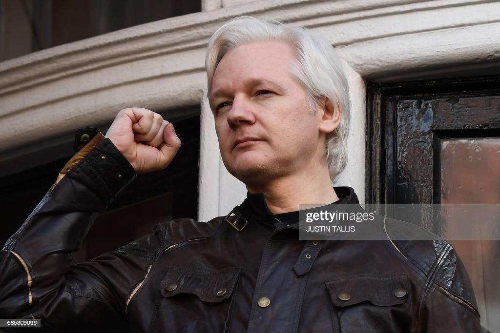 TOPSHOT - Wikileaks founder Julian Assange raises his fist prior to addressing the media on the balcony of the Embassy of Ecuador in London on May 19, 2017. Ecuador urged Britain today to 'grant safe passage' out of the country to WikiLeaks founder Julian Assange after Sweden dropped a warrant that drove him to take refuge in Ecuador's London embassy. / AFP PHOTO / Justin TALLIS