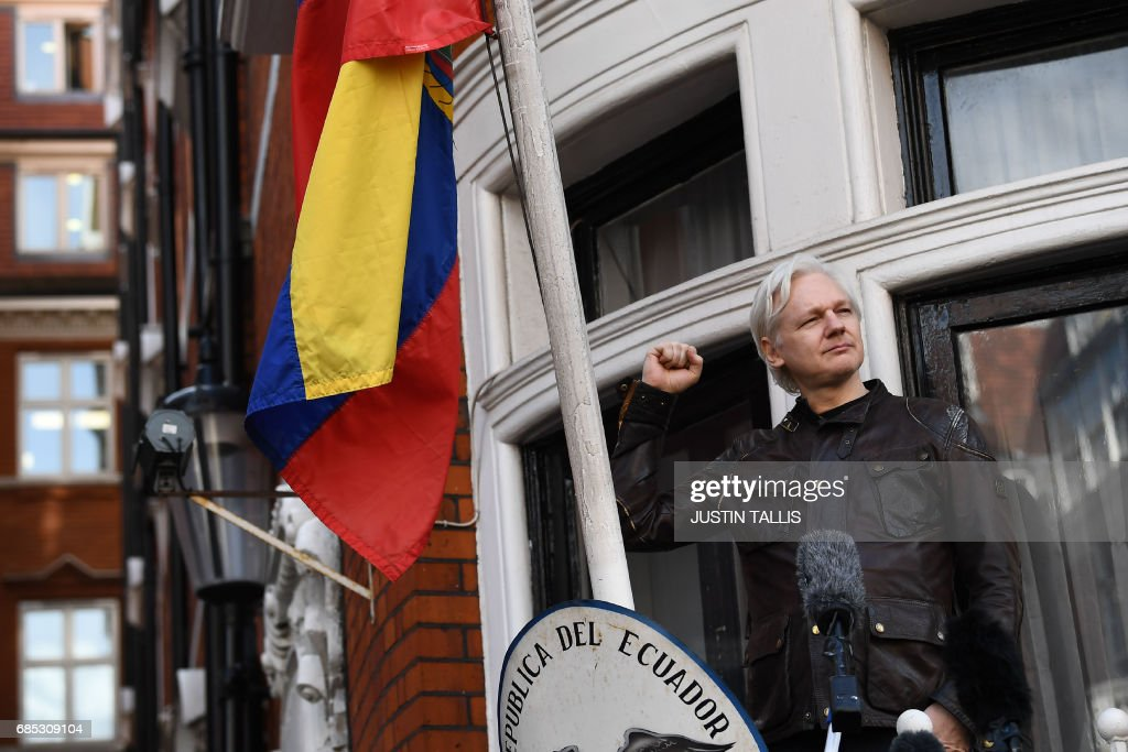 Wikileaks founder Julian Assange raises his fist prior to addressing the media on the balcony of the Embassy of Ecuador in London on May 19, 2017. Ecuador urged Britain today to 'grant safe passage' out of the country to WikiLeaks founder Julian Assange after Sweden dropped a warrant that drove him to take refuge in Ecuador's London embassy. / AFP PHOTO / Justin TALLIS