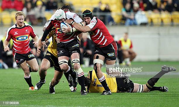 Wikus van Heerden of the Lions runs the ball with teammate Warren Whitely in support during the round 16 Super Rugby match between the Hurricanes and...