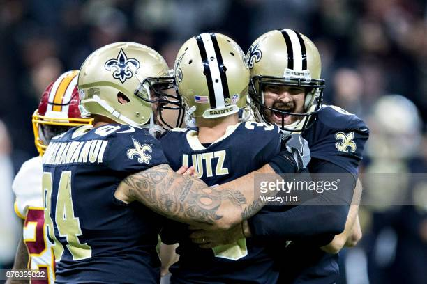 Wil Lutz is hugged by teammates Michael Hoomanawanui and Chase Daniels of the New Orleans Saints after kicking the winning field goal against the...