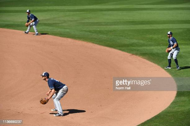 Wil Myers, Luis Urias and Greg Garcia of the San Diego Padres shift to the right side of the infield during the fifth inning of a spring training...