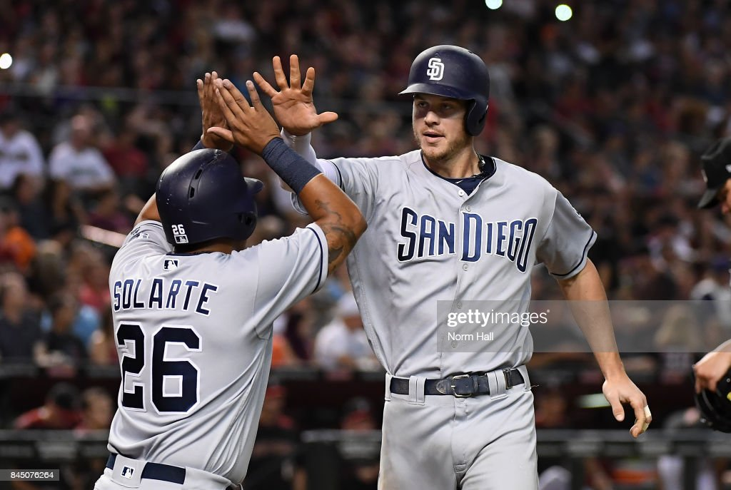 Wil Myers #4 of the San Diego Padres celebrates with teammate Yangervis Solarte #26 after hitting a two run home run off of Zack Godley #52 of the Arizona Diamondbacks during the seventh inning at Chase Field on September 9, 2017 in Phoenix, Arizona.