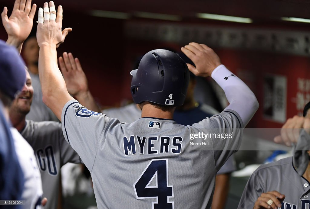 Wil Myers #4 of the San Diego Padres celebrates with teammates in the dugout after hitting a two run home run off of Zack Godley #52 of the Arizona Diamondbacks during the seventh inning at Chase Field on September 9, 2017 in Phoenix, Arizona. Padres won 8-7.