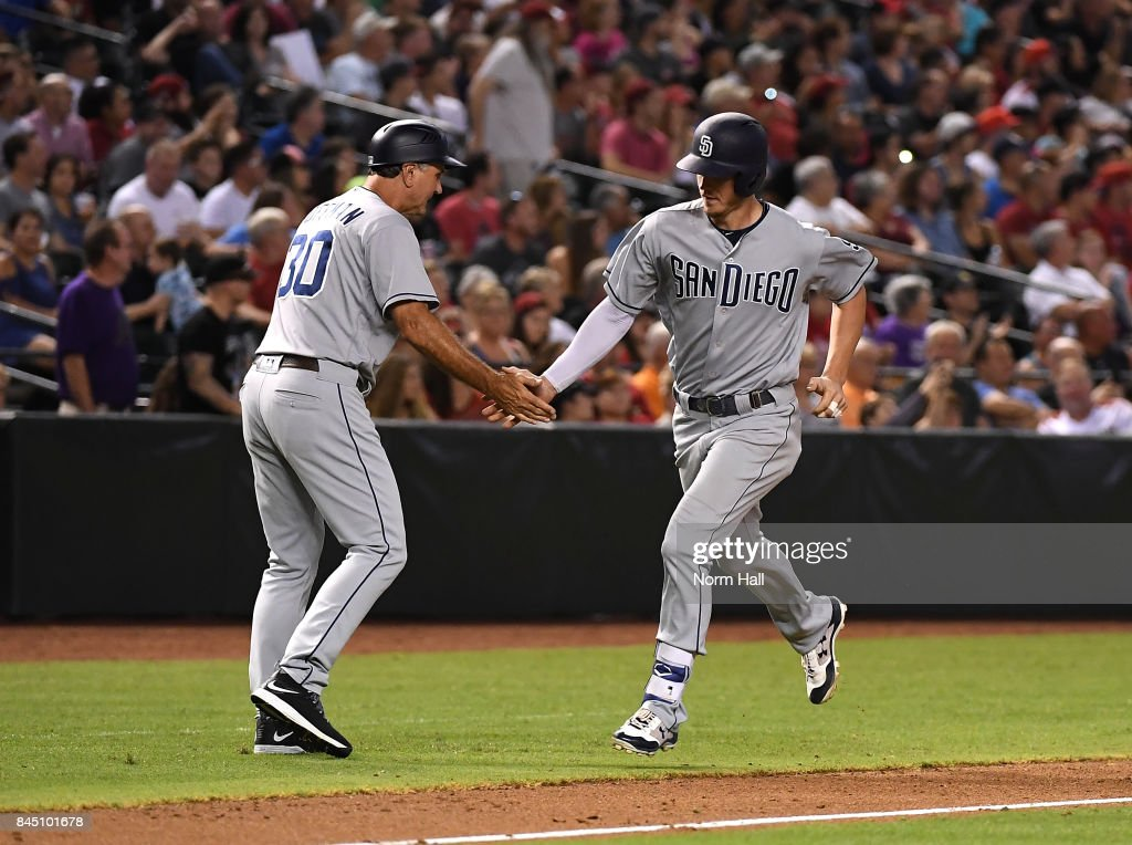 Wil Myers #4 of the San Diego Padres celebrates with third base coach Glenn Hoffman #30 after hitting a two run home run off of Zack Godley #52 of the Arizona Diamondbacks during the seventh inning at Chase Field on September 9, 2017 in Phoenix, Arizona. Padres won 8-7.