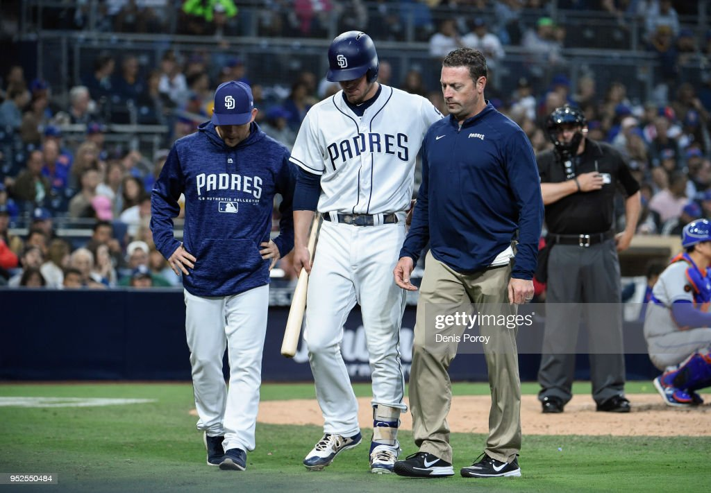 Wil Myers #4 of the San Diego Padres, center, walks off the field next to manager Andy Green, left, and a trainer during the fifth inning of a baseball game against the New York Mets at PETCO Park on April 28, 2018 in San Diego, California. Meyers left the game.
