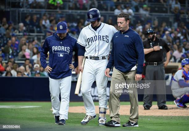 Wil Myers of the San Diego Padres center walks off the field next to manager Andy Green left and a trainer during the fifth inning of a baseball game...