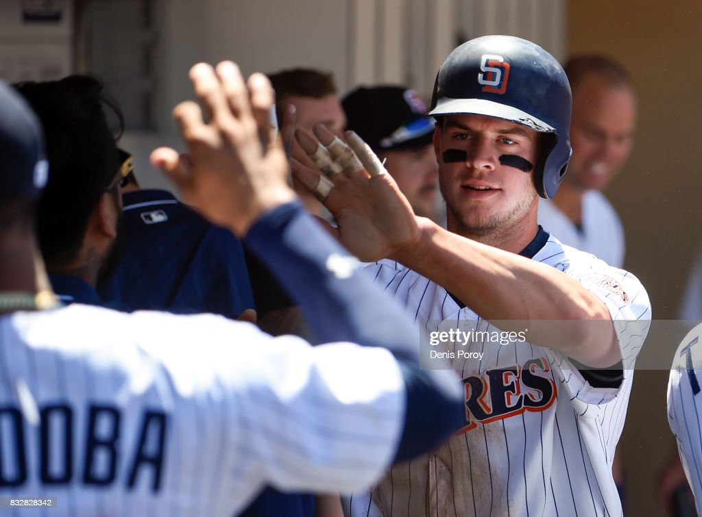 Wil Myers #4 of the San Diego Padres is congratulated after scoring during the fourth inning of a baseball game against the Philadelphia Phillies at PETCO Park on August 16, 2017 in San Diego, California.