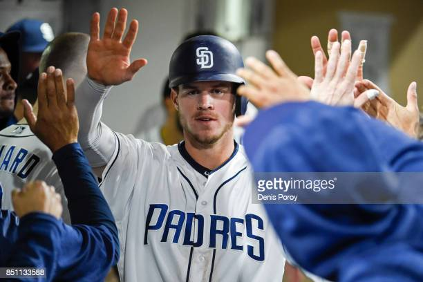 Wil Myers of the San Diego Padres is congratulated after scoring during the sixth inning of a baseball game against the Colorado Rockies at PETCO...