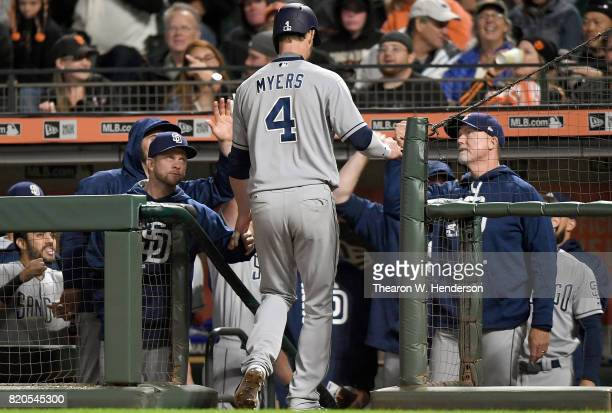 Wil Myers of the San Diego Padres is congratulated by manager Andy Green and bench coach Mark McGwire after Myers hit a solo home run against the San...
