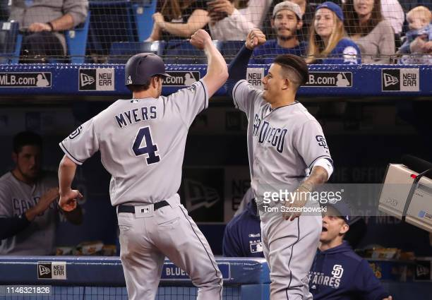 Wil Myers of the San Diego Padres is congratulated by Manny Machado after hitting a solo home run in the second inning during MLB game action against...