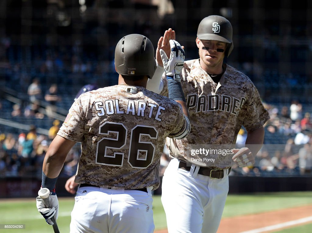 Wil Myers #4 of the San Diego Padres is congratulated by Yangervis Solarte #26 after hitting a solo home run during the first inning of a baseball game against the Colorado Rockies at PETCO Park on September 24, 2017 in San Diego, California.