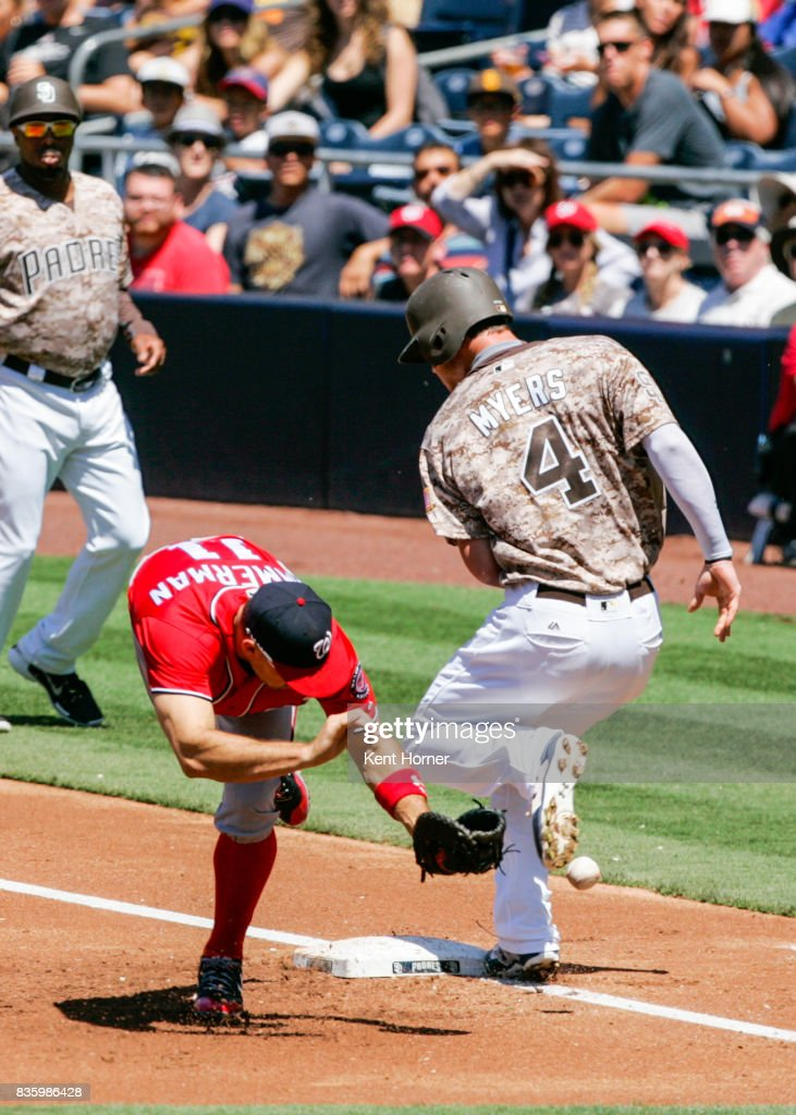 Wil Myers #4 of the San Diego Padres is safe at first base during the first inning as Ryan Zimmerman #11 of the Washington Nationals is unable to catch the ball at PETCO Park on August 20, 2017 in San Diego, California.