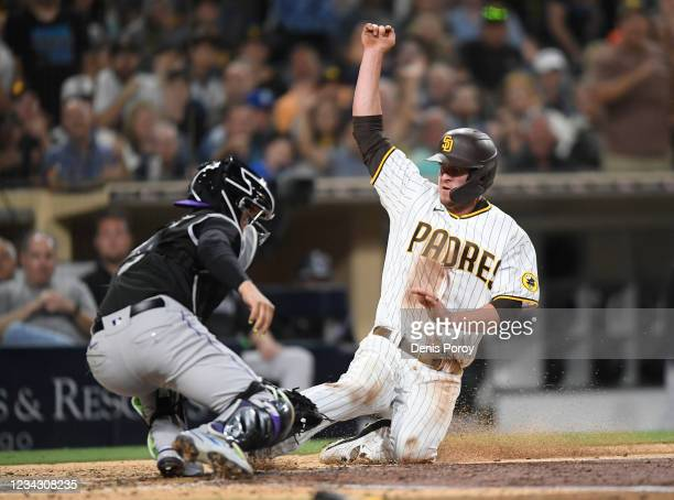 Wil Myers of the San Diego Padres is tagged out at the plate by Dom Nunez of the Colorado Rockies during the sixth inning of a baseball game at Petco...