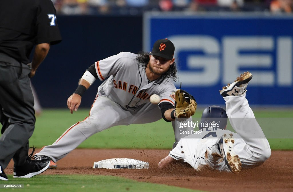 Wil Myers #4 of the San Diego Padres is tagged out by Brandon Crawford #35 of the San Francisco Giants as he tries to steal second base during the second inning of a baseball game at PETCO Park on August 28, 2017 in San Diego, California.