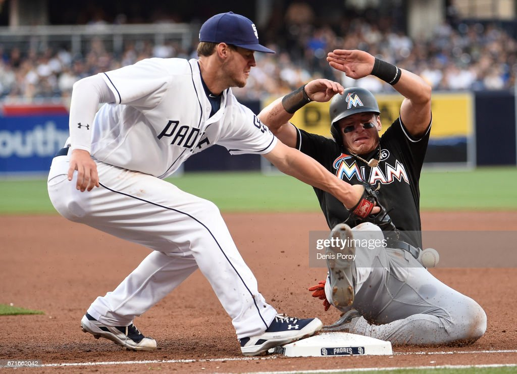 Wil Myers #4 of the San Diego Padres loses the ball as Derek Dietrich #32 of the Miami Marlins gets back to first base during the fifth inning of a baseball game at PETCO Park on April 22, 2017 in San Diego, California.
