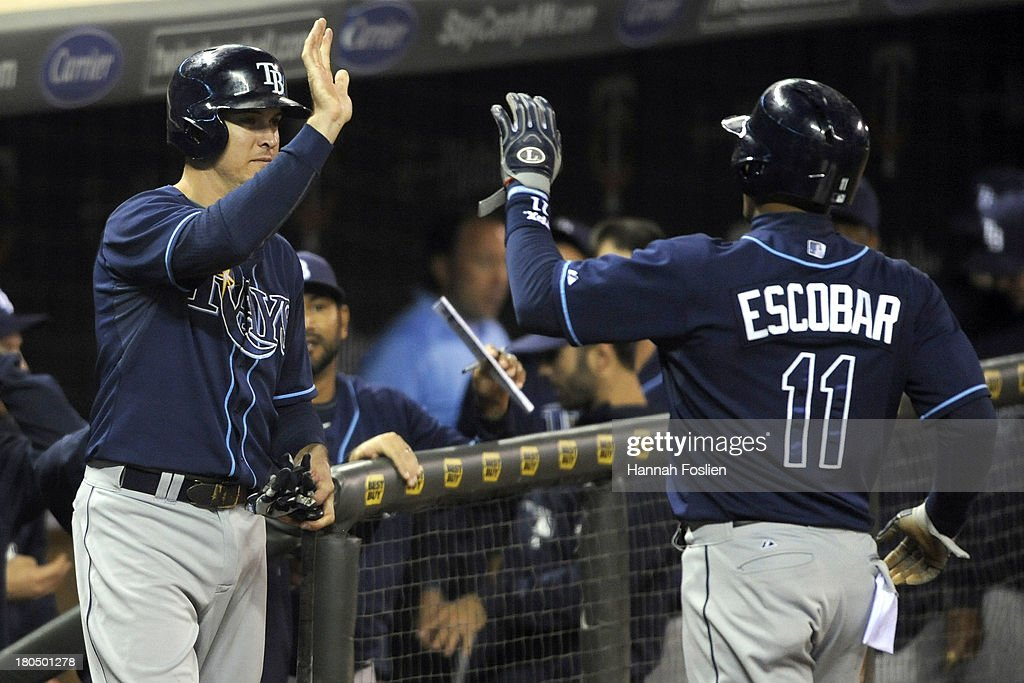 Wil Myers #9 of the Tampa Bay Rays congratulates teammate Yunel Escobar #11 on scoring a run against the Minnesota Twins during the third inning of the game on September 13, 2013 at Target Field in Minneapolis, Minnesota.