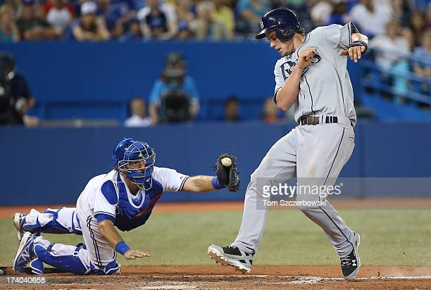Wil Myers of the Tampa Bay Rays evades the tag of JP Arencibia of the Toronto Blue Jays to score a run in the ninth inning during MLB game action on...