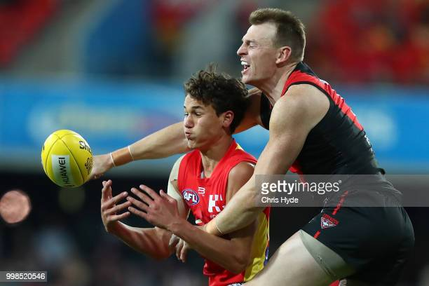 Wil Powell of the Suns and Brendon Goddard of the Bombers compete for the ball during the round 17 AFL match between the Gold Coast Suns and the...