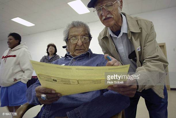 TO'HAJIILEE NM NOVEMBER 2 Wilbert Hunt the oldest member of the Pueblo of Acoma reviews a sample ballot with the help of his nephew Eddie Hunt before...