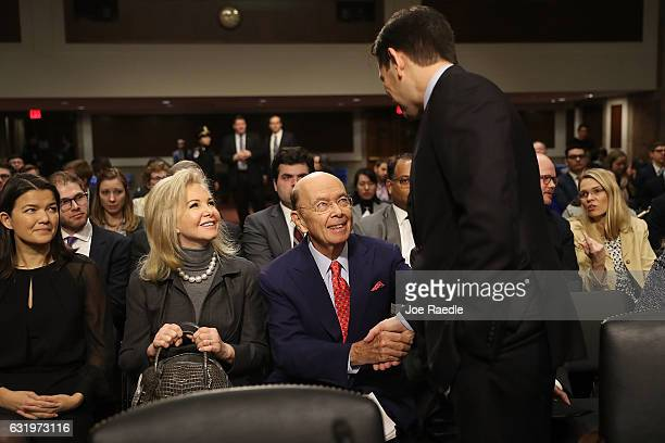 Wilbur Ross picked by Presidentelect Donald Trump to serve as his commerce secretary sits with his wife Hilary Geary Ross as he shakes hands with Sen...