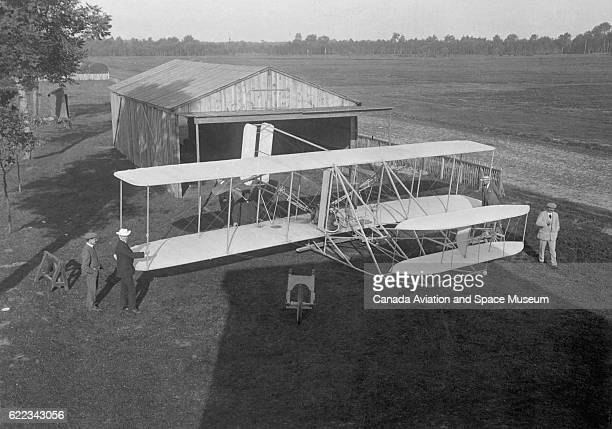 Wilbur Wright and a few other men with a Wright Flyer biplane outside a hangar | Location Near Le Mans France
