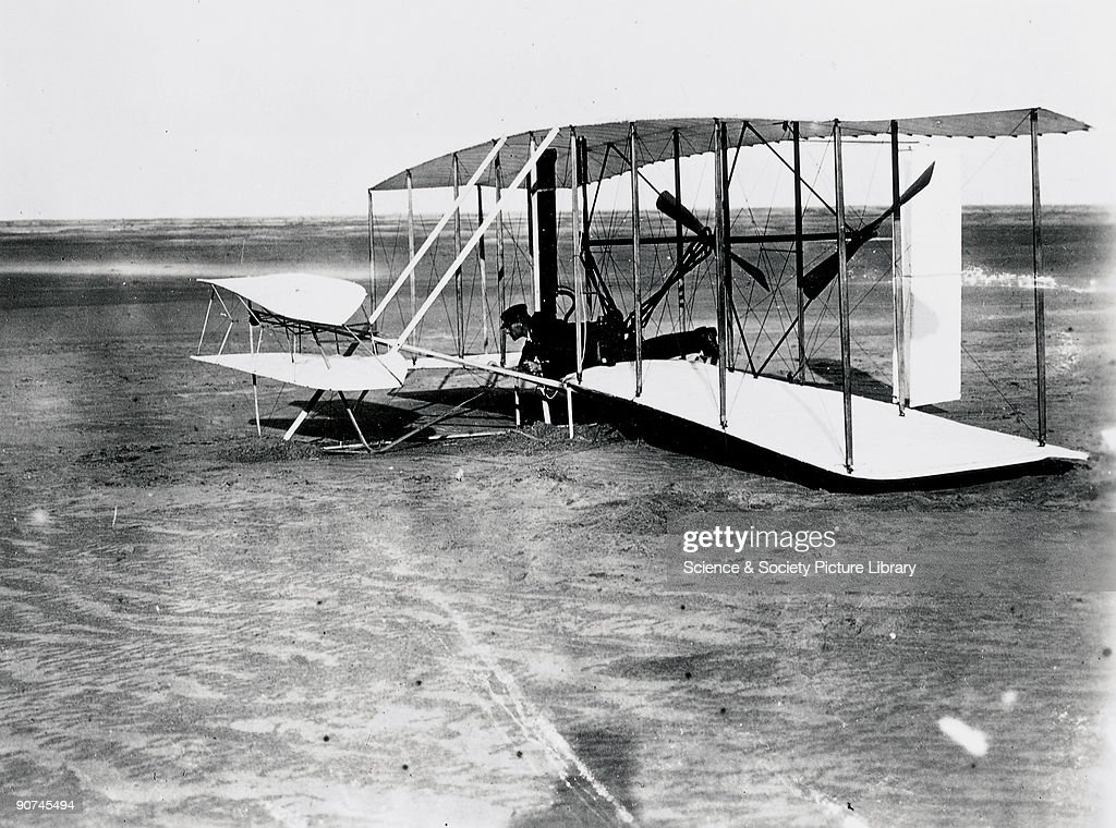 Wilbur Wright (1867-1912) at the controls of the 'Flyer' at Kitty Hawk, North Carolina, United States. Orville Wright and his brother Wilbur (1867-1912) were self-taught American aeroplane pioneers. After extensive experiments with kites and gliders, the Wright Brothers arrived at a design for an aircraft capable of sustained controlled flight. They than added a petrol engine to the aircraft, which they christened the 'Flyer', in 1903. Three days after their first, unsuccessful attempt, the Flyer achieved the first sustained powered flight, with Orville piloting, on 17 December 1903. Their success at Kitty Hawk encouraged the brothers to abandon their cycle business and patent their flying machine, forming an aircraft production company in 1909.