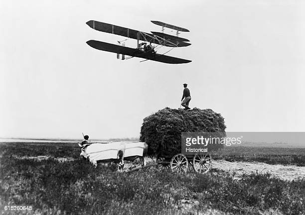 Wilbur Wright flies the distinctive Wright Brothers' biplane over a French farm A man stands atop a hay wagon and views the aircraft