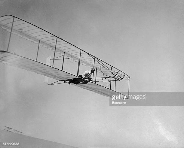 Wilbur Wright glides on the north slope of Big Kill Devil Hill with a double-ruddered glider, at Kitty Hawk on October 2, 1902.
