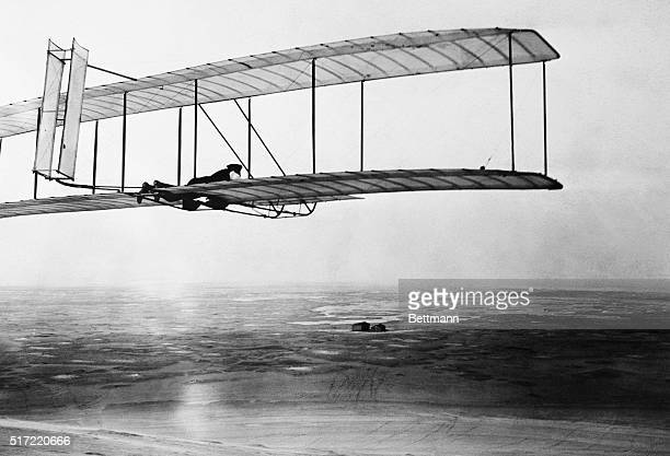 Wilbur Wright pilots a glider with a movable double rear vertical rudder over the Kill Devil Hills near Kitty Hawk. The Wright Brothers' camp can be...