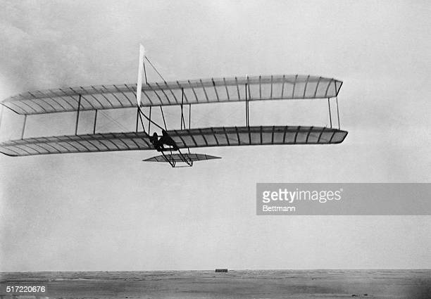 Wilbur Wright pilots a glider with single vertical rear rudder at Kill Devil Hills, North Carolina, in 1902. The Wrights' camp building is on the...