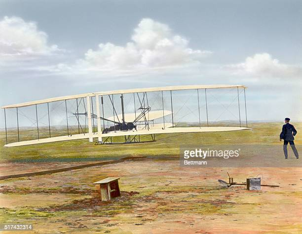Wilbur Wright watches Orville Wright pilot the first successful heavierthanair flight in the Wright Flyer at Kitty Hawk North Carolina on December 17...