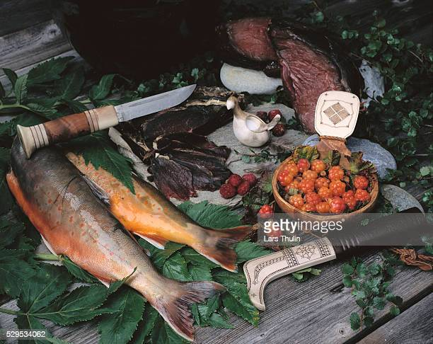 Wild berries, fish and antique knife on table