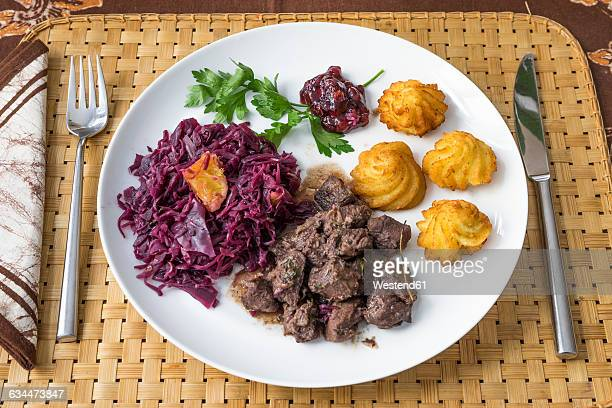 Wild boar goulash with red cabbage, croquette, lingonberry and parsley on plate