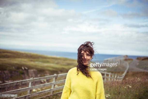 wild hair blows in girls face on remote coastline - road trip stock pictures, royalty-free photos & images