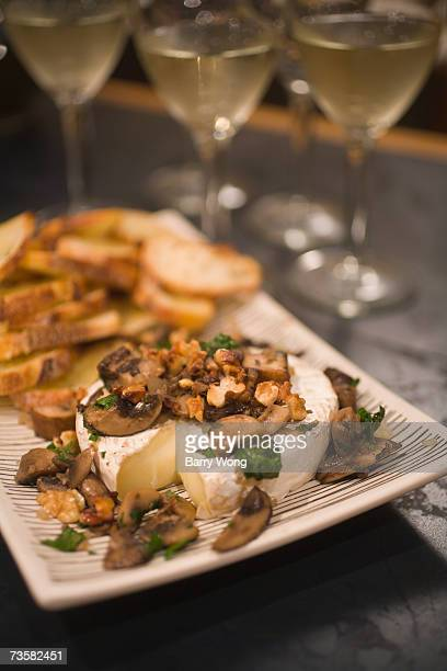 Wild mushroom, walnut and cheese appetizer served with crostini, and glasses of white wine