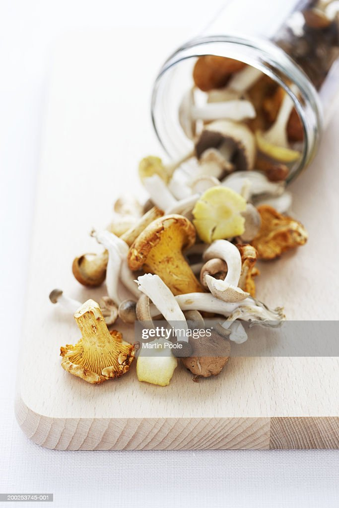 Wild mushrooms in jar and on wooden board, close-up : Stock Photo