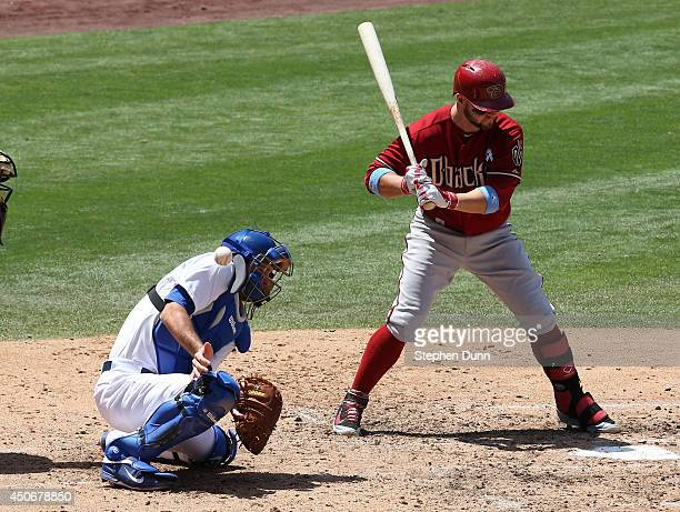 A wild pitch thrown by Josh Beckett gets past catcher Drew Butera of the Los Angeles Dodgers as Cody Ross of the Arizona Diamondbacks bats allowing a...
